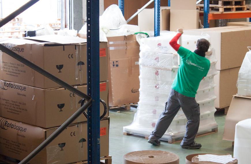 Gestión logística. Trabajador haciendo embalaje de cajas de productos por rotomoldeo en almacén de Rotobasque